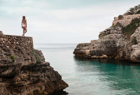Rear view of young woman in bikini looking out from Cala en Brut, Menorca, Balearic islands, Spain LANG_EVOIMAGES