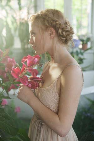 adentro y afuera: Retrato de mujer joven, cabello rubio trenzado, con flores rosas