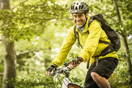 Happy mature male mountain biker cycling in forest