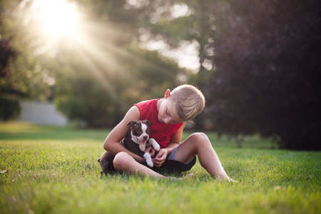 pooches: Front view of boy sitting on grass holding Boston Terrier puppy, looking down