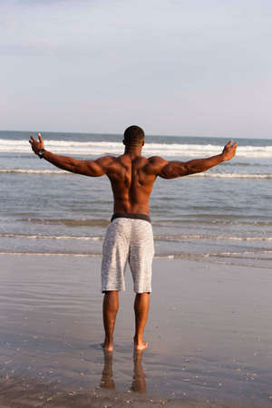 Mid adult man standing on beach, arms outstretched, rear view