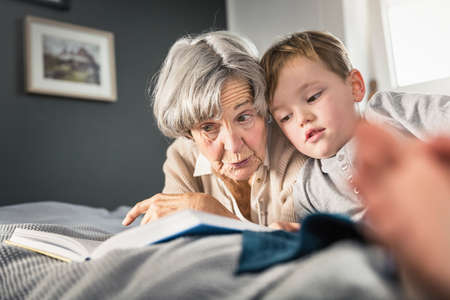 Senior woman reading to grandson on bed