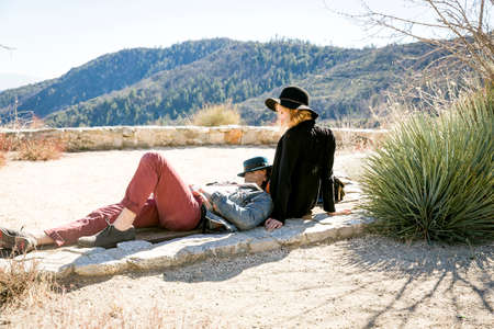 Young couple relaxing on viewing platform overlooking mountains, Chilao Campgrounds, Los Angeles, California, USA