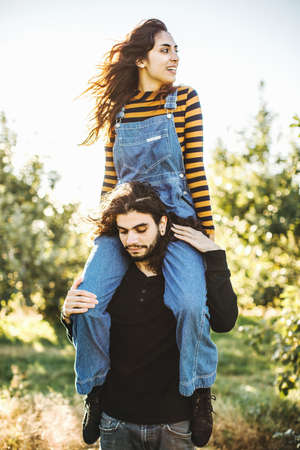 Young couple in rural environment, young woman sitting on mans shoulders