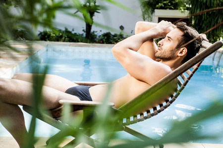 Man reclining on sunlounger by swimming pool LANG_EVOIMAGES