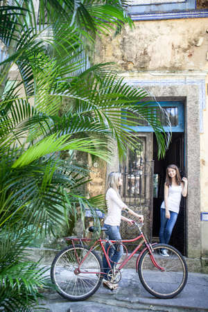 Young woman with bicycle talking to friend in doorway,Rio de Janeiro,Brazil