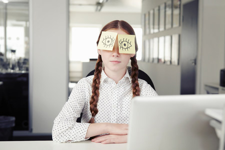 Girl in office with adhesive notes covering eyes