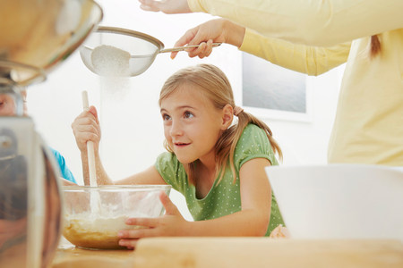 Children baking,sieving flour into mixing bowl