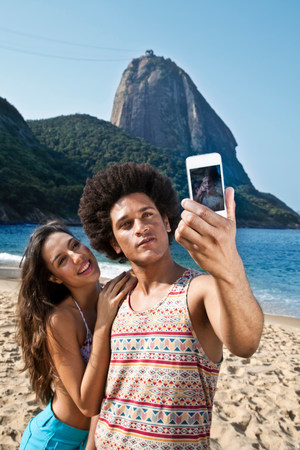 brazilian ethnicity: Couple photographing themselves on beach with camera phone,Rio de Janeiro,Brazil LANG_EVOIMAGES