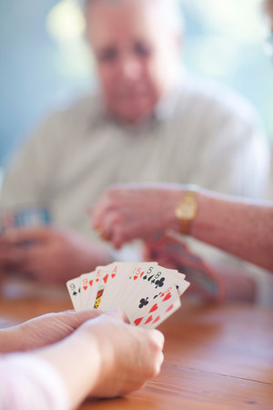 people: Senior male playing cards with family LANG_EVOIMAGES