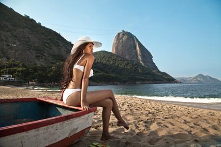 brazilian ethnicity: Woman sitting on boat on beach,Rio de Janeiro,Brazil LANG_EVOIMAGES