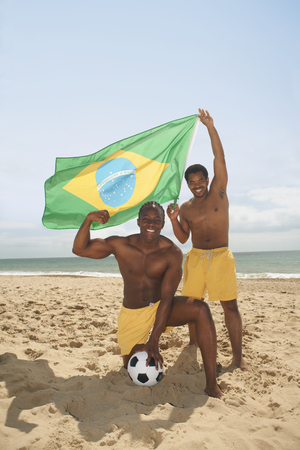 Men posing with brazilian flag on beach