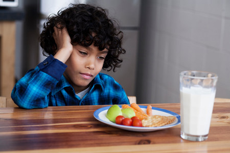 Boy staring at snacks and glass of milk LANG_EVOIMAGES