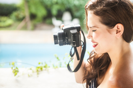 vintage: Young woman looking through camera viewfinder LANG_EVOIMAGES