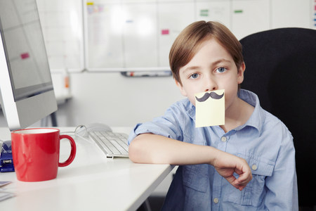 Boy with adhesive note covering mouth,drawing of moustache