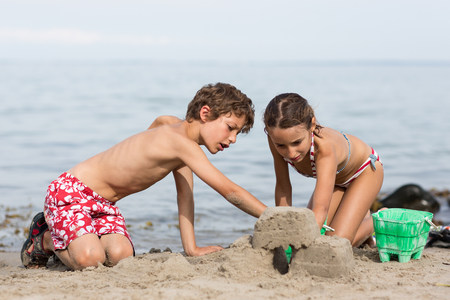 Brother and sister on beach building sandcastle
