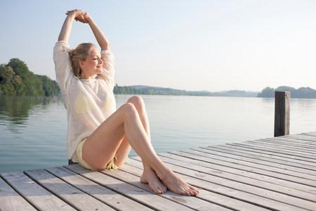 mujer mirando el horizonte: Mujer joven relajante en el muelle del lago