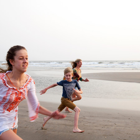 Mother,son and daughter running on beach