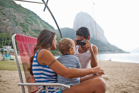 Man taking photograph of mother and son on chair,Rio de Janeiro,Brazil LANG_EVOIMAGES