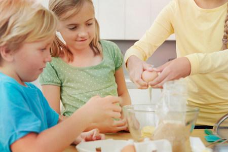 Children baking,breaking eggs into bowl