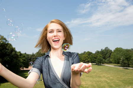 Young woman having fun with bubbles in park LANG_EVOIMAGES