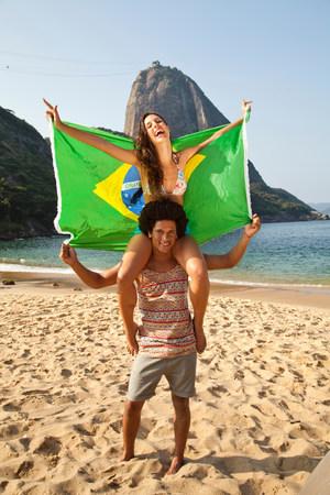 brazilian ethnicity: Couple on beach with Brazilian flag,Rio de Janeiro,Brazil