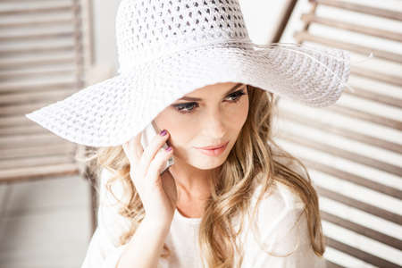 Glamorous young woman in sun hat,using cellphone
