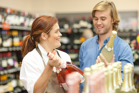 Female shop assistant advising customer on wine