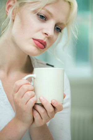 Wistful looking young woman with a coffee LANG_EVOIMAGES