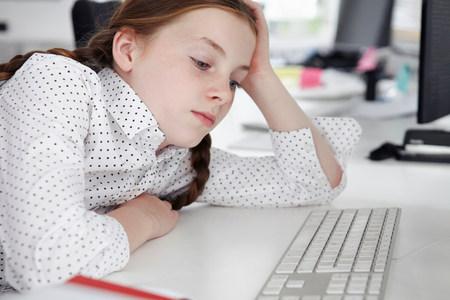 Girl staring at computer keyboard