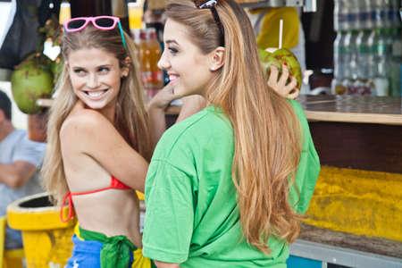 brazilian ethnicity: Two happy young women at beach kiosk,Ipanema Beach,Rio,Brazil LANG_EVOIMAGES
