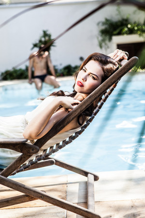 Young woman reclining in sunlounger at poolside LANG_EVOIMAGES