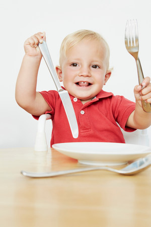 Boy holding cutlery with empty plate
