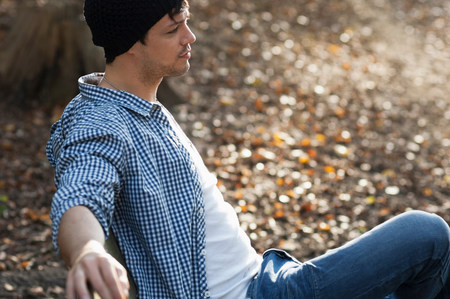 Portrait of man sitting on bench in autumn LANG_EVOIMAGES