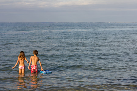 Brother and sister paddling in sea