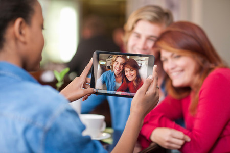Group of friends in cafe taking photograph with digital tablet