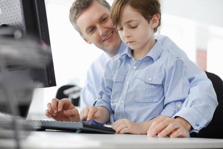 Boy sitting on fathers lap using computer keyboard