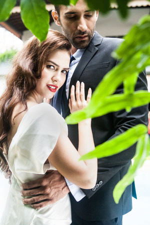 Woman looking over shoulder touching mans chest