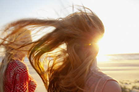 Mother and daughter on windy beach,close up LANG_EVOIMAGES