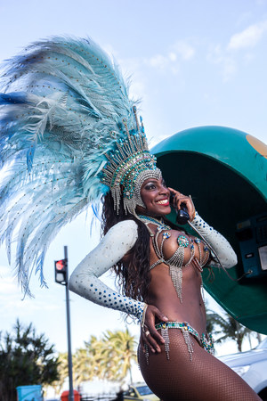 brazilian ethnicity: Samba dancer using pay phone,Ipanema Beach,Rio De Janeiro,Brazil LANG_EVOIMAGES