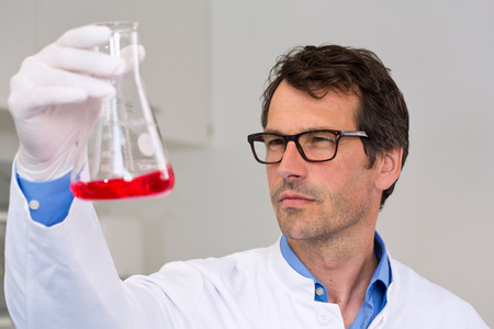 one mature man only: Male scientist examining ph-reaction of liquid in flask