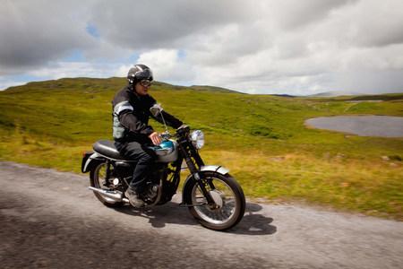 65 69 years: Senior male on motorbike on rural road