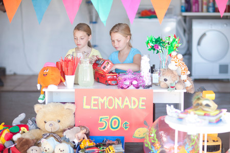Two young sisters setting up stall