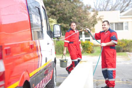 hosepipe: Paramedics cleaning ambulance with hosepipe