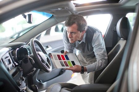 Mid adult man with color swatch in car showroom