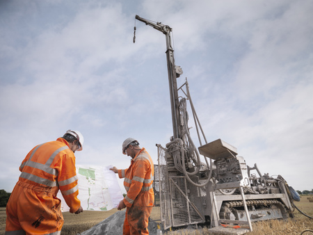 Drilling rig workers inspecting map in field LANG_EVOIMAGES