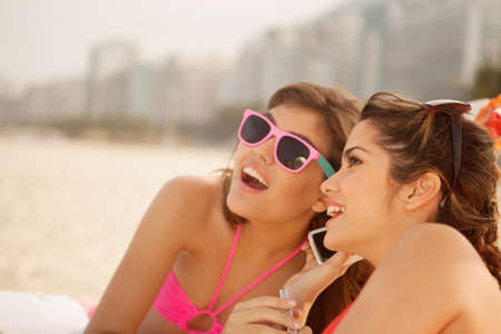 brazil beach swimsuit: Young women chatting on mobile phone on beach LANG_EVOIMAGES