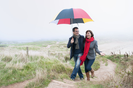 path to romance: Couple on coast walk carrying umbrella,Thurlestone,Devon,UK