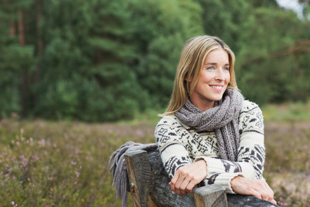Mid adult woman wearing sweater on bench