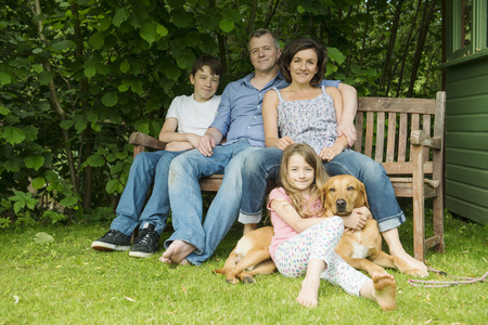 10 15 years: Portrait of family with two children sitting on garden bench with dog LANG_EVOIMAGES